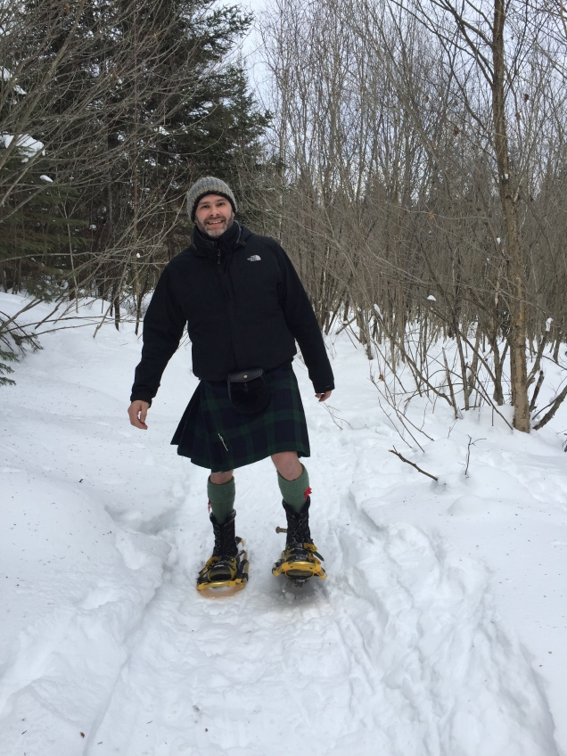 Jade Sambrook snowshoeing in the countryside wearing a Scottish kilt
